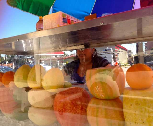 Los Angeles fruit stand with a rainbow umbrella.